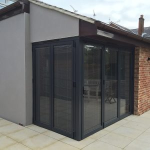 Anthracite grey aluminium bi-folding doors, floating corner.